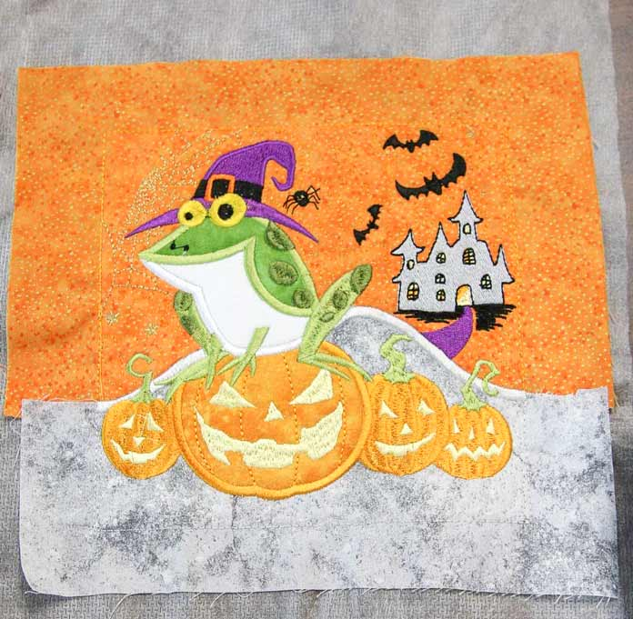 Machine embroidery applique and machine embroidered Halloween block ready to be trimmed; using the HUSQVARNA VIKING Designer Brilliance 80 sewing machine to finish it.