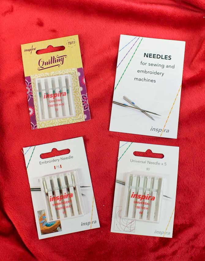 Various types and sizes of sewing machine needles by Inspira, as well as an information booklet.