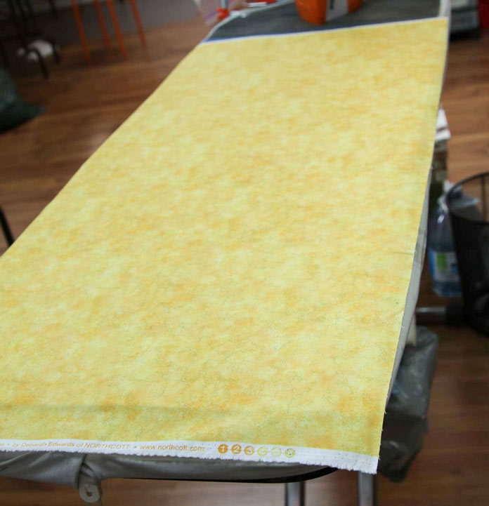 Press the backing (from the middle) of the three layers of the table runner to be quilted.