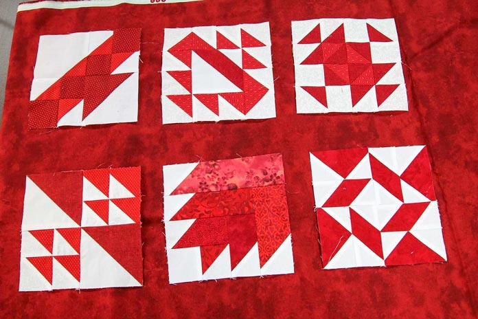 Auditioning some of the blocks on the red sashing fabric