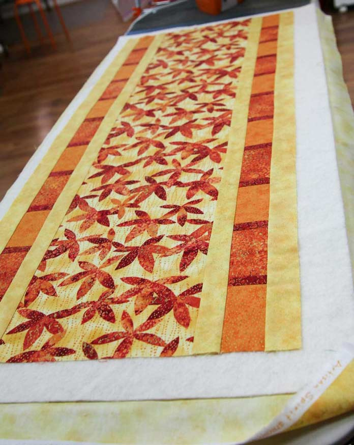 Three layers of a small project to be quilted are laid out on the ironing board.