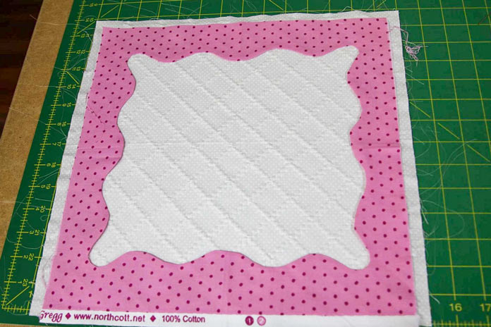 The edges of the pink frame are turned under and ready to be appliqued in place; using the HUSQVARNA VIKING Designer Brilliance 80 sewing machine.