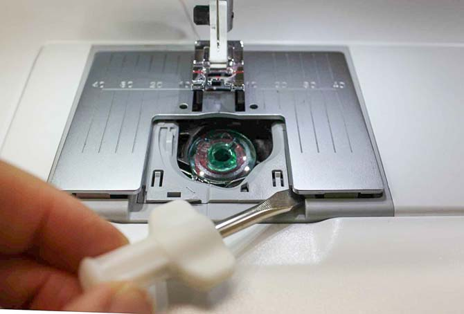 Use the screwdriver to remove the needle plate.
