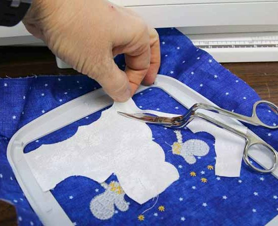 Using bent handled scissors to trim as close as possible to the tacking stitches
