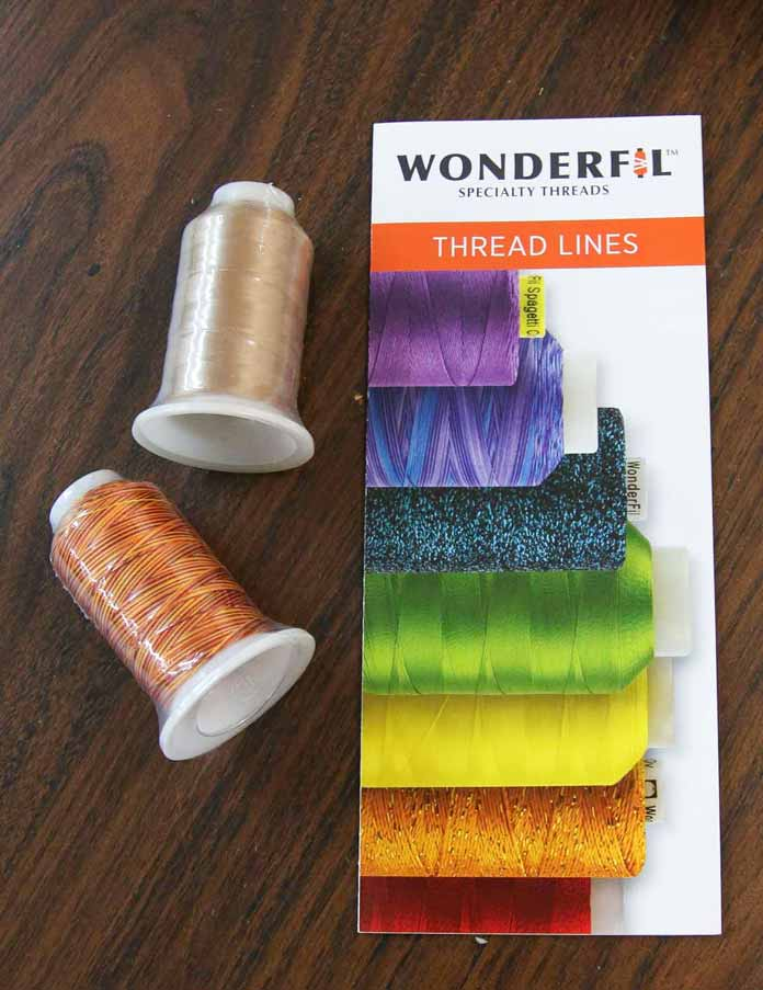 Two spools of Wonderfil thread and pamphlet outlining their thread line-up