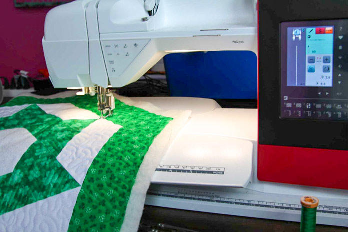 The green and white table topper is being quilted with lots of room to spare to the right of the needle