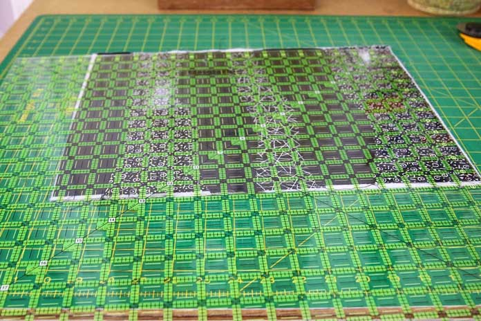 "Trimming the placemat with a large ruler (20½"" square)."