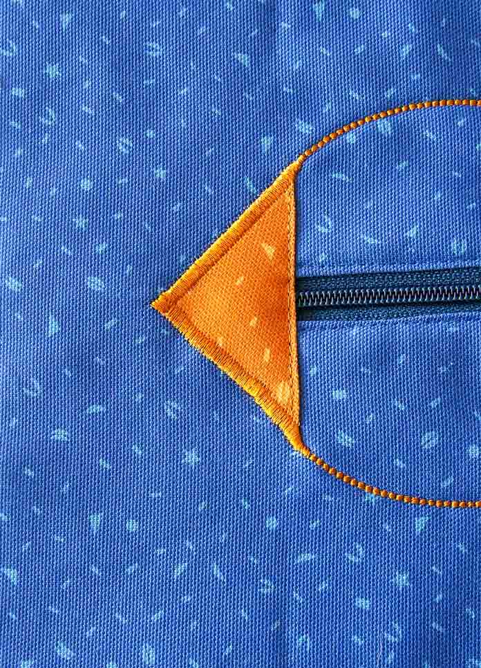 Decorative zipper stop using a satin stitch that blends into the machine embroidery
