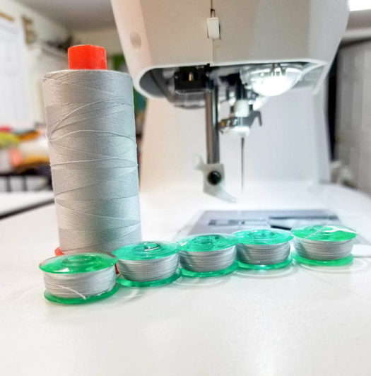 Five bobbins are wound and ready to sew.