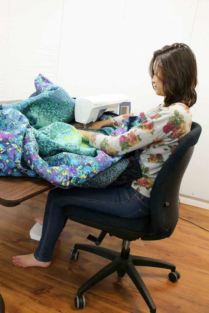 Note the position of the quilter's arms. They're sort of splayed out from her body. Kept in this position and moving a quilt around, she would soon get a lot of fatigue in her shoulders. Her chair needs to be raised in order to bring her arms tighter to her body.