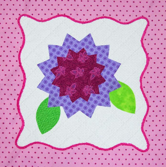 The flower (minus the center) is now fused to the block. All that's left is to choose some applique stitches to stitch down the leaves and the two flower pieces. So close. Using the HUSQVARNA VIKING Designer Brilliance 80 sewing machine