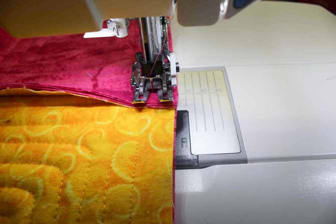 Running a line of stitching around the edge of the quilt