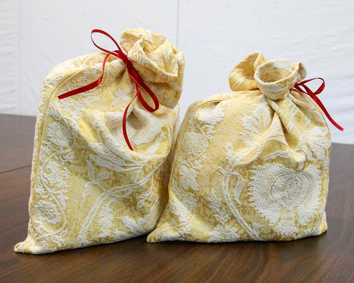 Two elegant gift bags tied with bright red ribbon