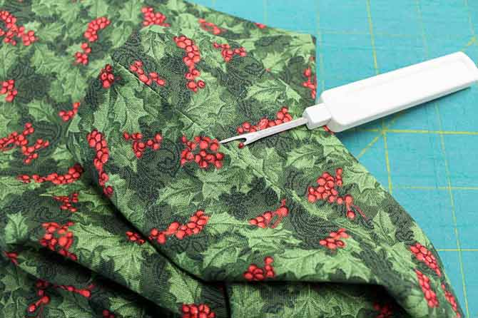 Use the seam ripper to open the side seams between the two rows of stitching that forms the casing.