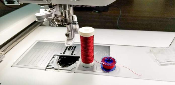 The embroidery foot is attached and I have a red thread for the top and the bobbin.