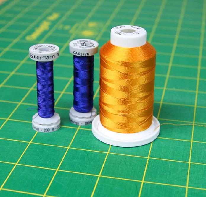 Two small spools of blue embroidery Gütermann thread and one big spool of gold embroidery thread; HUSQVARNA VIKING Designer Brilliance 80 sewing machine
