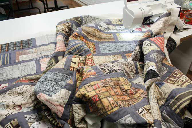 Quilt is supported on the left by the extension surface of the quilting table