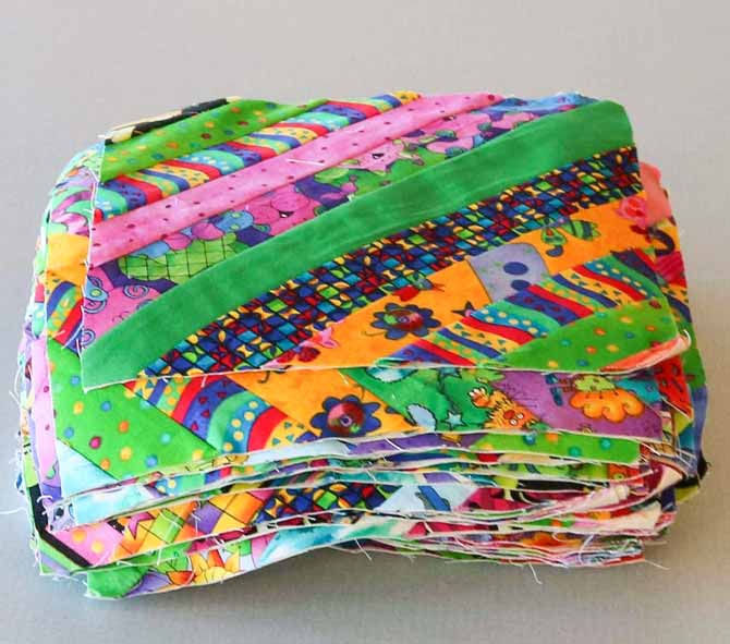Bundle of string pieced blocks made with brightly colored fabric strings