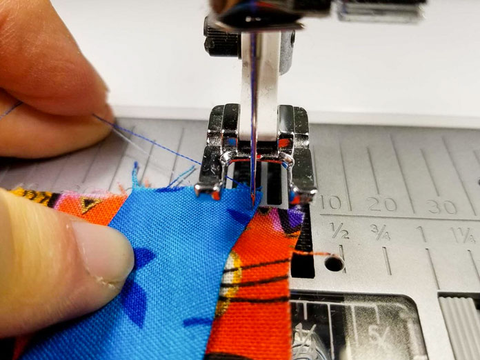 Hold the threads as you start to prevent thread nests on the underside of the work