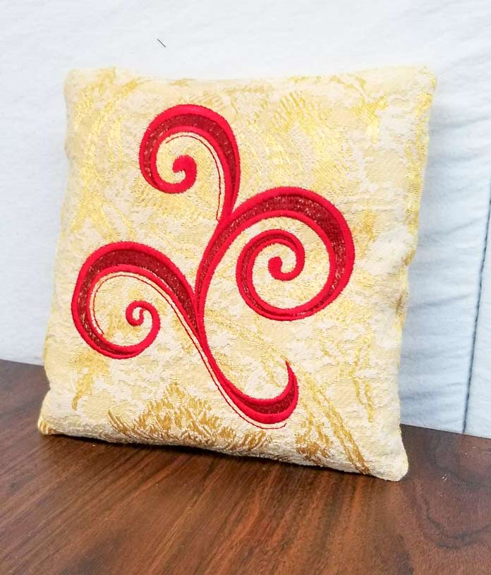 A decorative cushion made with embroidery and recycled fabrics