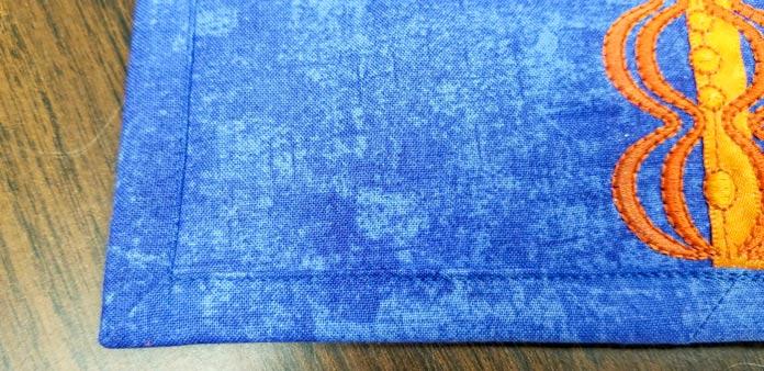 The binding on the front of the mug rug