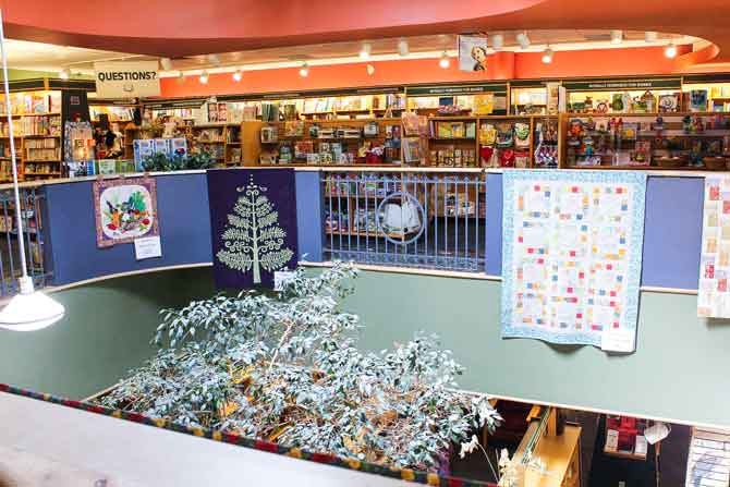 Quilts hang from the balcony at McNally Robinson