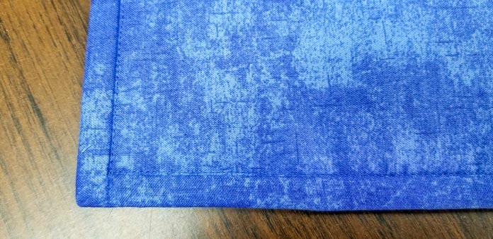 The binding on the back of the mug rug