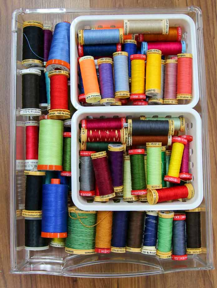A drawer full of various colors of thread