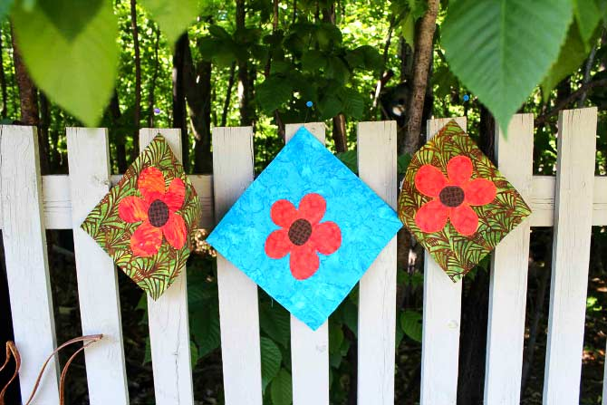 Three appliqued flowers from our post of June 6, 2014 on QUILTsocial.