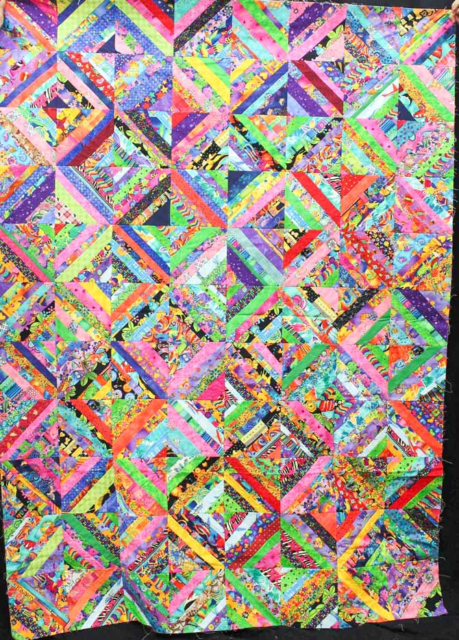 String pieced quilt with bright prints. Eight blocks wide by eleven rows