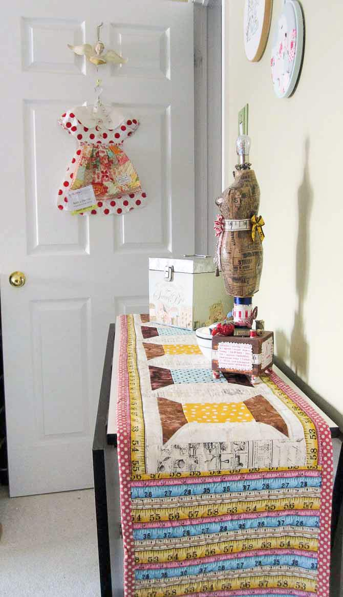 The finished table runner now decorates my Studio Collection space saving design/cutting table in my sewing space. When it's folded up, it takes up less space than the bookshelf it replaced. And, it's way more useful!