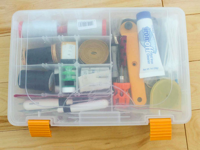 Small plastic storage box for basic sewing tools and supplies