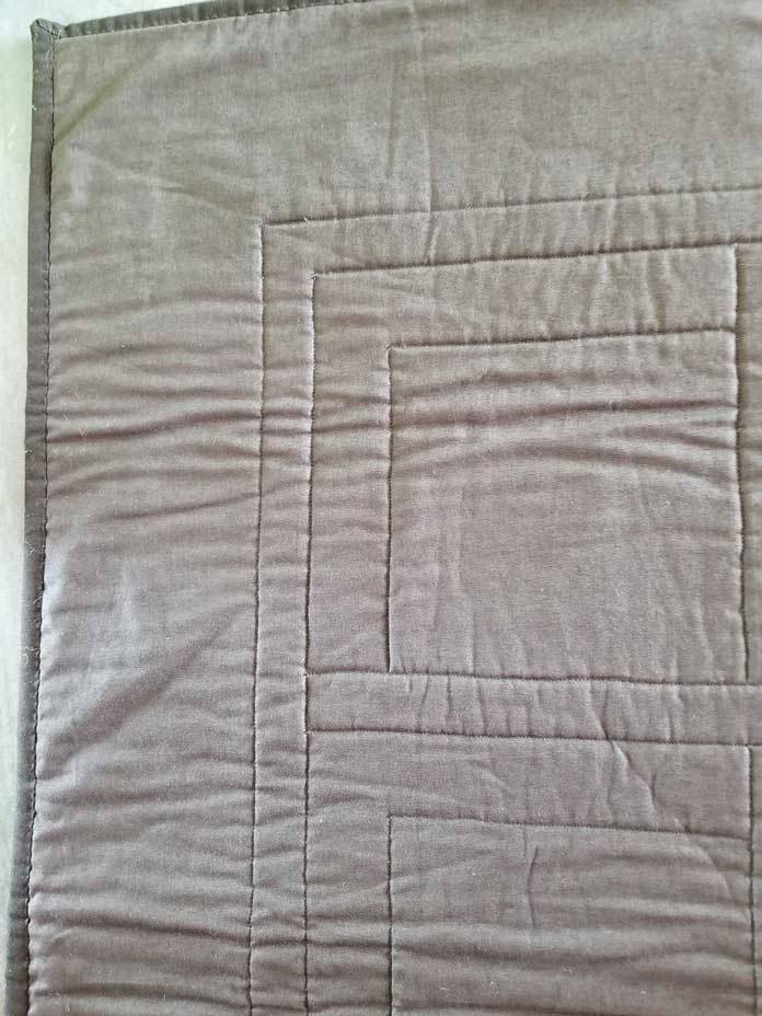 The back of the wallhanging, which shows only the straight lines of quilting, are completed.
