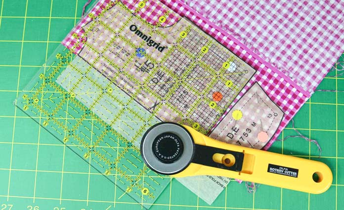 Using a ruler and rotary cutter to cut out a pattern piece for a doll shirt