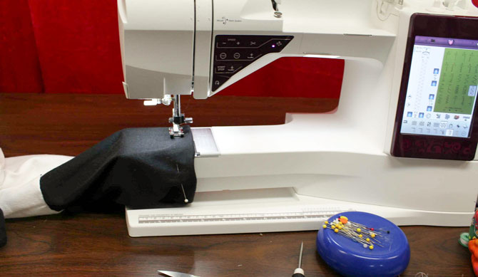 Hemming the sleeves on the T-shirt. You can see the free arm mode of the Designer Ruby Royale