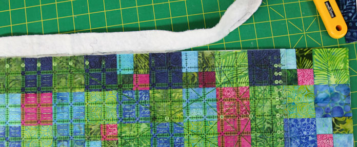 Using a long ruler to trim the edges of a quilt.