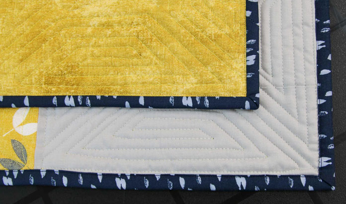 Using a straight stitch to attach the binding to the front of the quilt