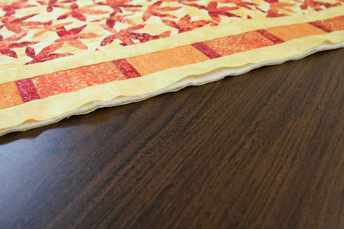 There's no stitching along the edges of this table runner to secure the three layers together.