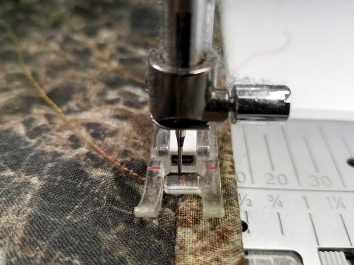 Using a clear B foot to stitch the binding to the front of the quilt