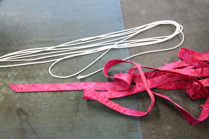Bias strips are pressed in half lengthwise and cording is steamed