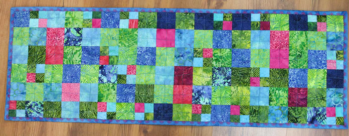 Completed table runner with decorative stitching on the binding