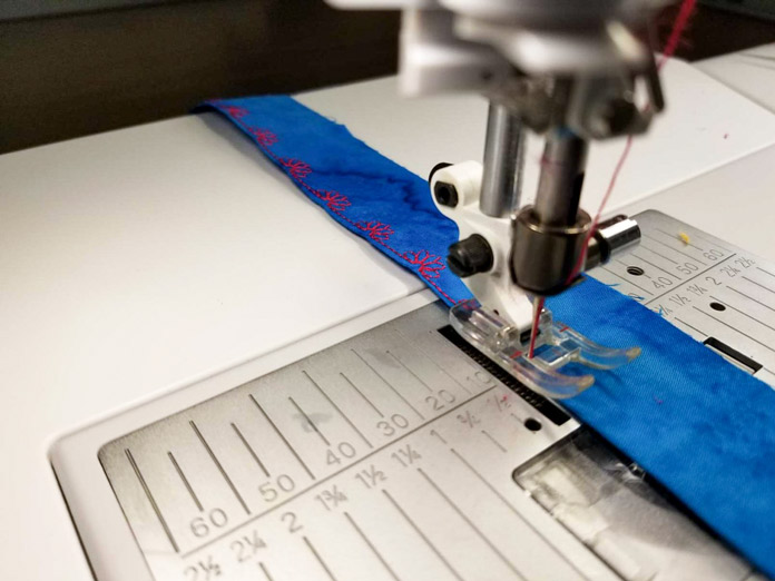 Sewing decorative stitches on a binding strip.