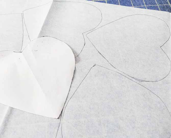 A freezer paper heart is used as a template for drawing on the paper side of fusible interfacing
