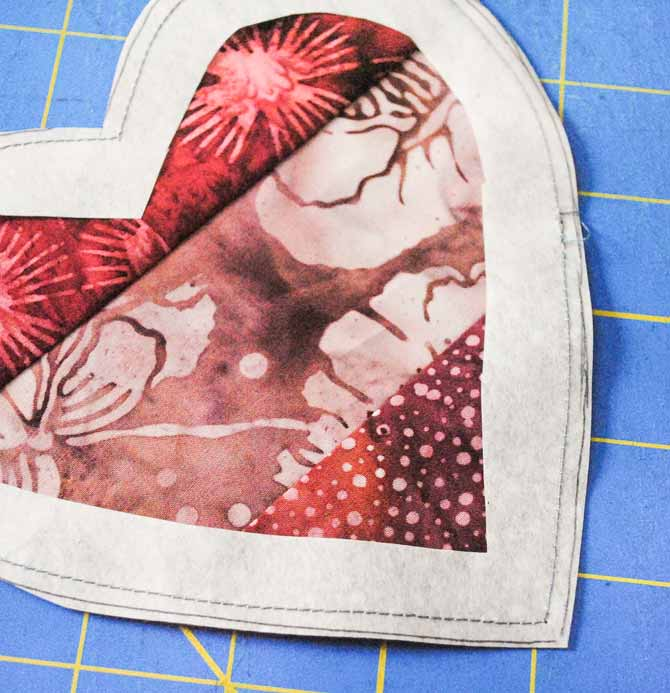 """The interfacing hearts are sewn to the right side of the strip set using a ⅛"""" seam then they're trimmed along the edge and the center of the interfacing is cut away."""