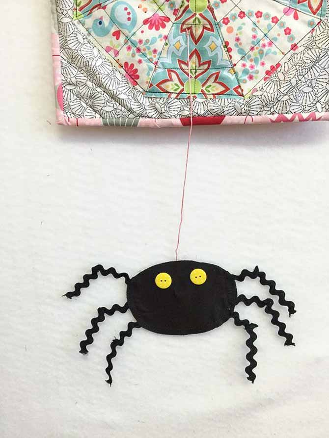 A quilt with a piece of embroidery thread hanging off of it and a fabric spider at the other end, all in black with rick rack legs.