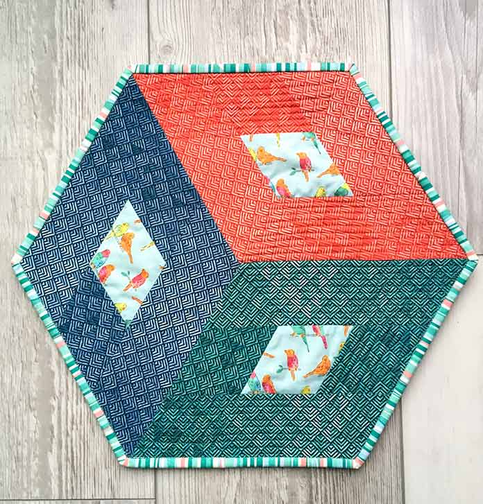A striped fabric when used for the binding on a hexagon quilt adds visual interest.