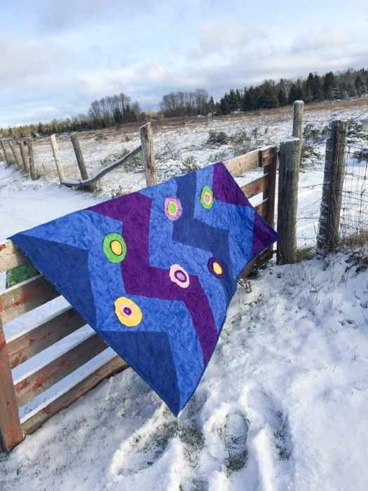 flannel quilt draped over wooden fence at farm.