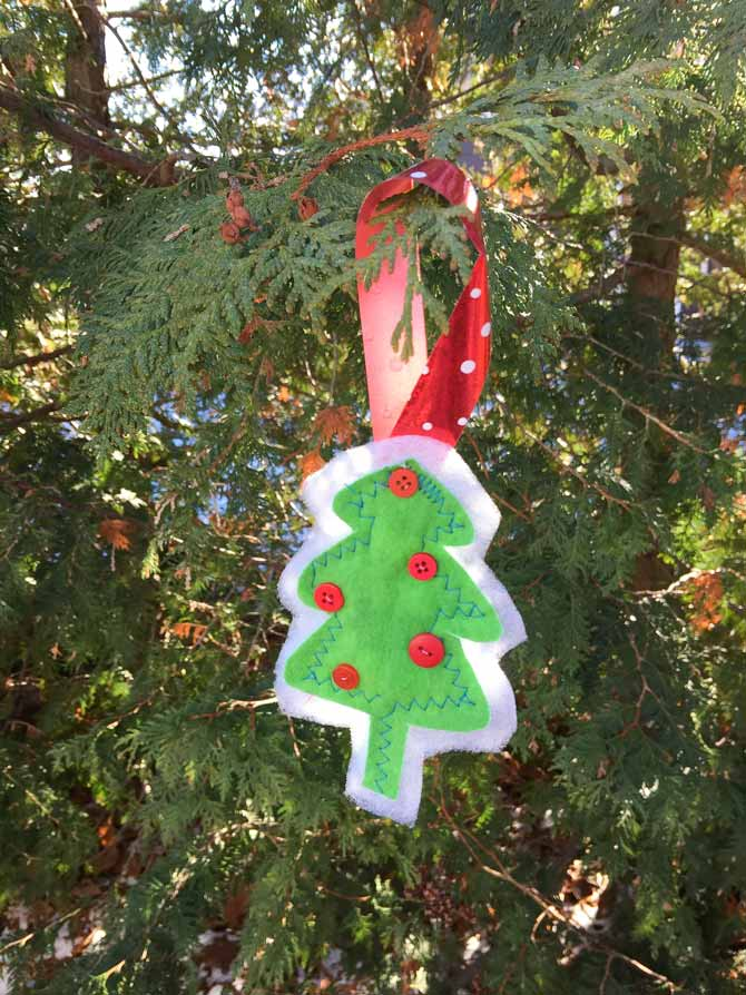 Small tree ornament made from green flannel with small red buttons on it hanging from a cedar tree.