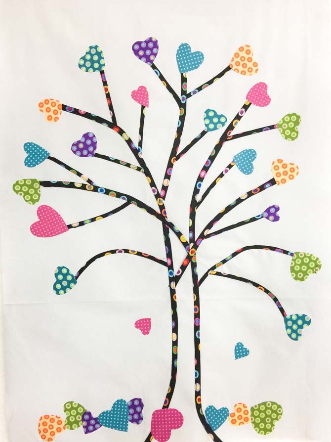 Fused hearts on a fabric tree made from bias tape on grey background.