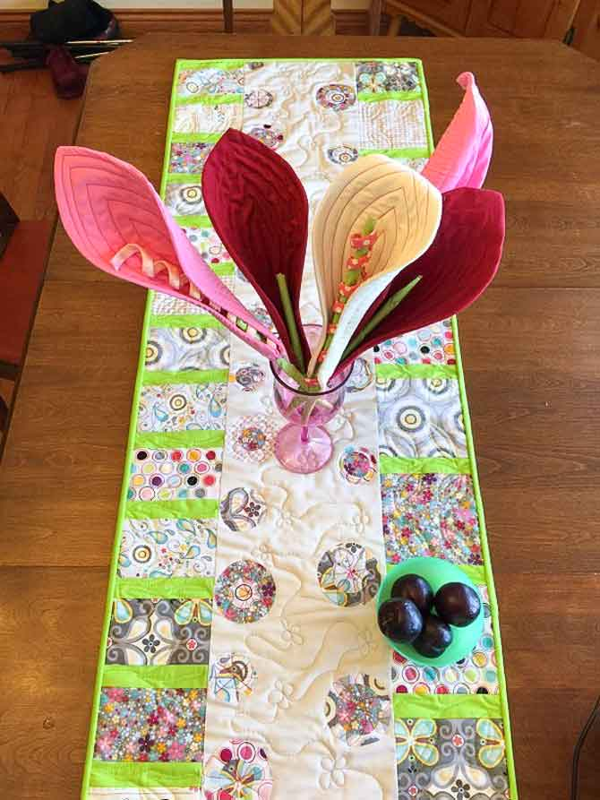 Modern table runner with fused flower circles and pieced stems.